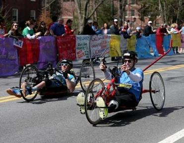 "Patrick Downes of Medford (right), who lost a leg last year, smiled as he rolled through the ""scream tunnel."""